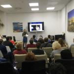 обучение в Чехии, на сцене стоит женщина в синем платье и ведет семинар